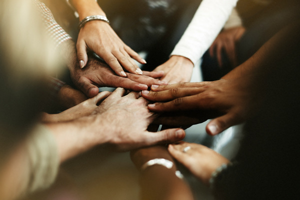 Numerous people putting their hands together in a circle.