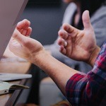 a man's hands raised over a desk