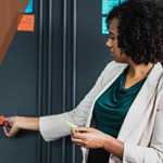 A female teacher placing an orange sticky note on the wall.